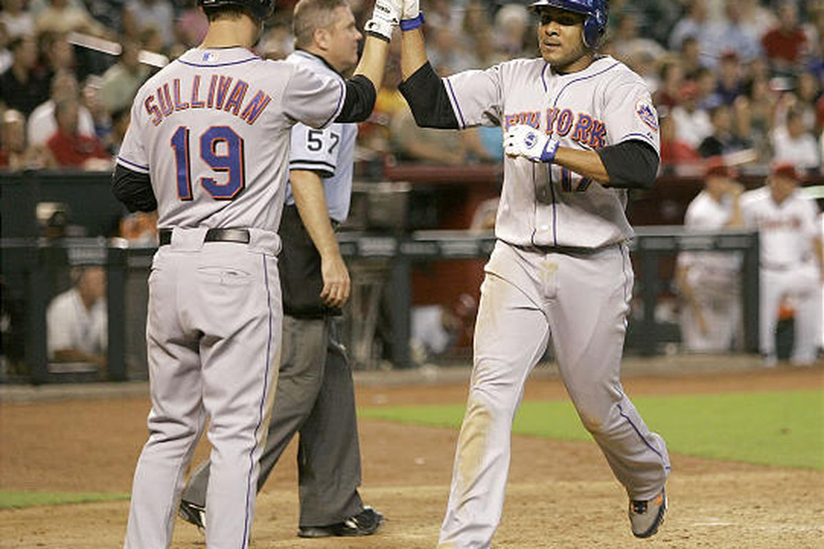 New York Mets' Fernando Tatis, right, high fives teammate Cory Sullivan (19) after scoring on an RBI single by Luis Castillo against the Arizona Diamondbacks during the eighth inning in Phoenix, Wednesday.