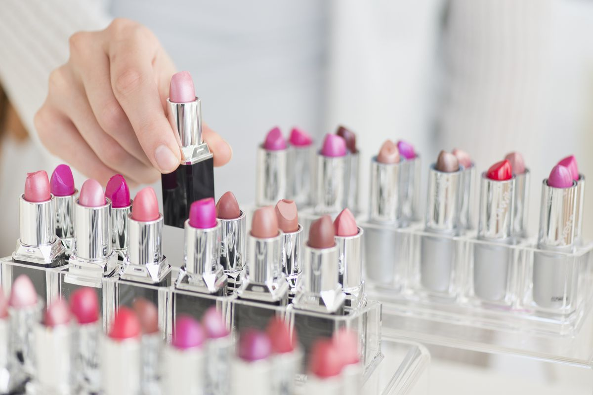 A woman picking up lipsticks from a counter display