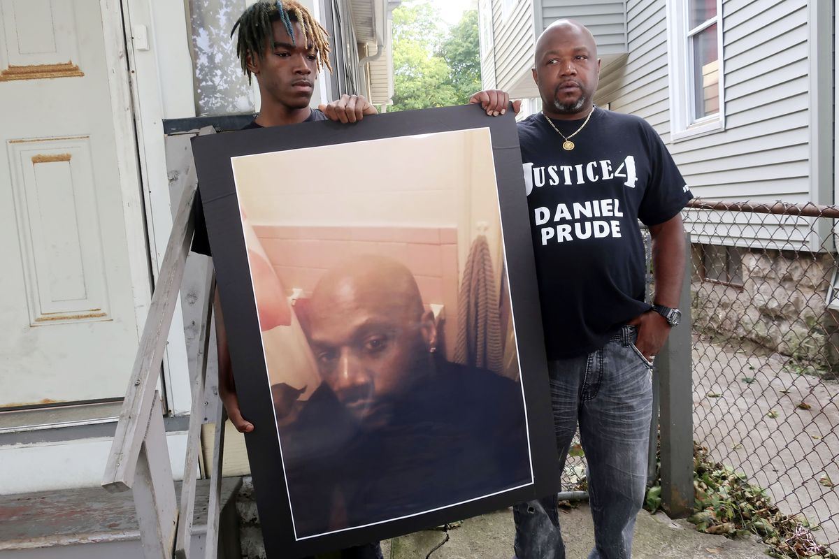 In this Sept. 3, 2020 file photo, Joe Prude, brother of Daniel Prude, right, and his son Armin, stand with a picture of Daniel Prude in Rochester, N.Y.