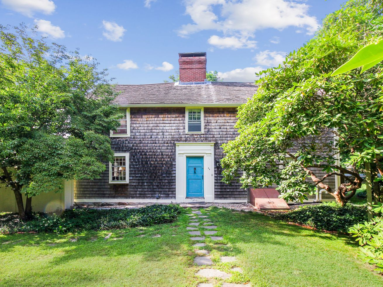 A rare home from 1682 sits on green grassy surrounded by bright green trees. The shingle-style home features a center brick chimney, white-framed windows, and a bright blue door trimmed in white.