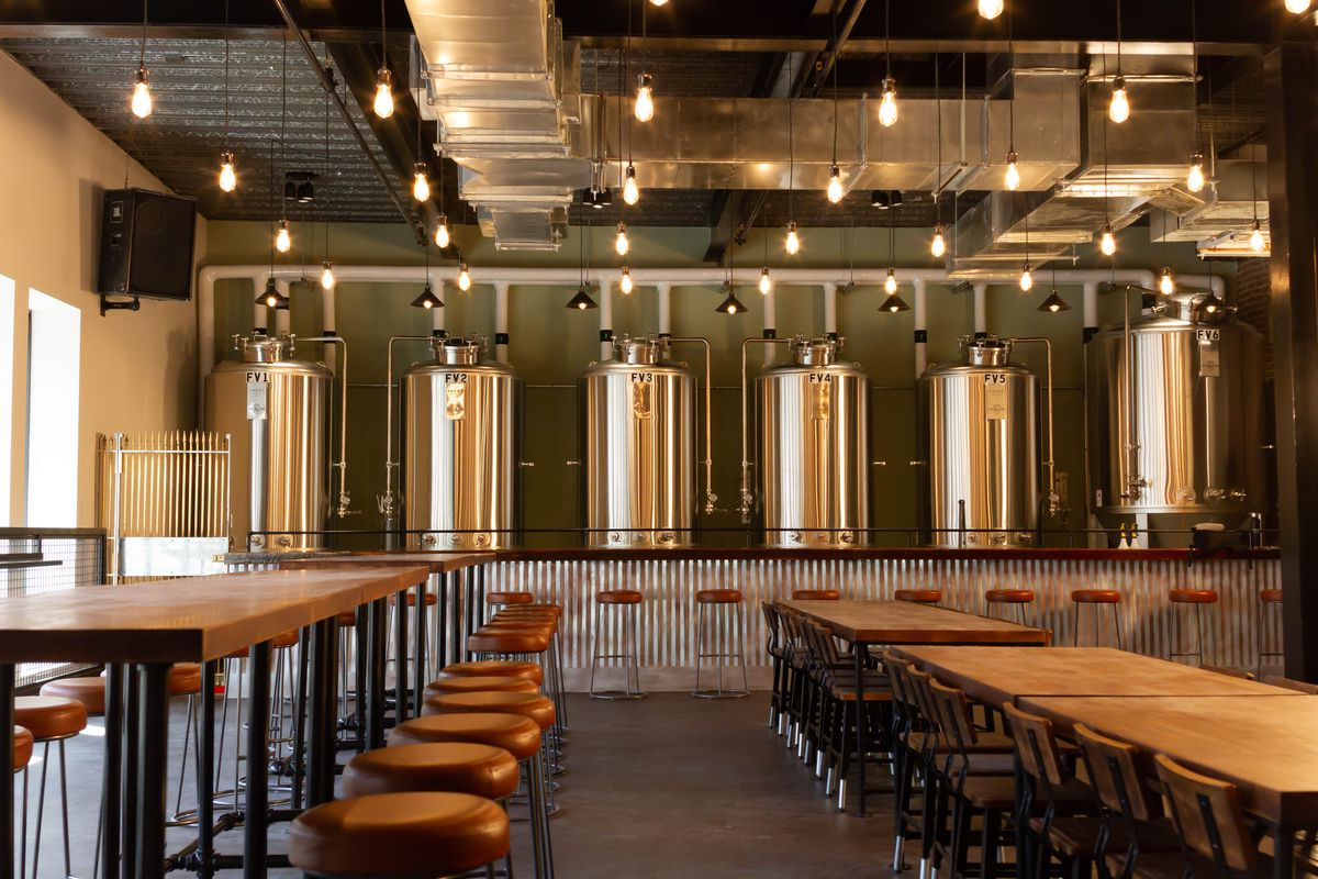 Interior view of a brewery's taproom, featuring long wooden tables and stools