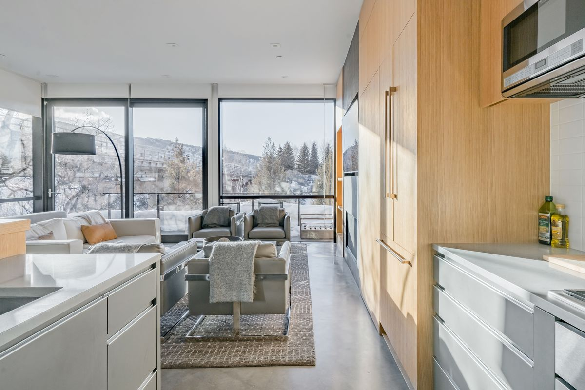 The view from a gray and white modern kitchen into a living room. The living room features gray chairs and views with snow and trees.