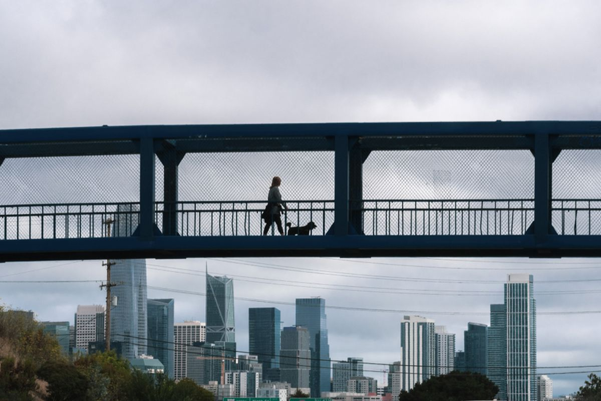 Silhouette of a woman walking her dog on a pedestrian overpass on a cloudy day; Tall buildings in San Francisco's financial district are visible in the background.