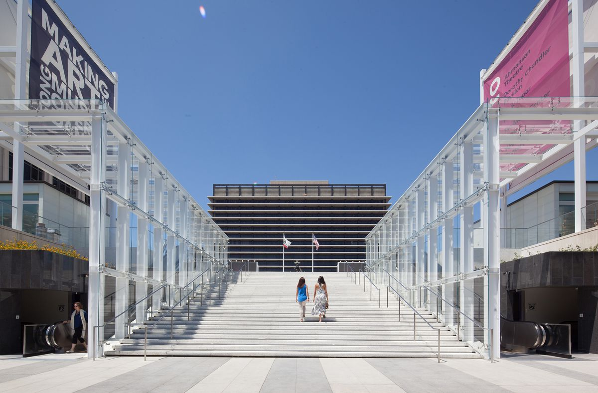 A photo of two women walking up a large outdoor staircase. On either side of them are glass structures covering two escalators.