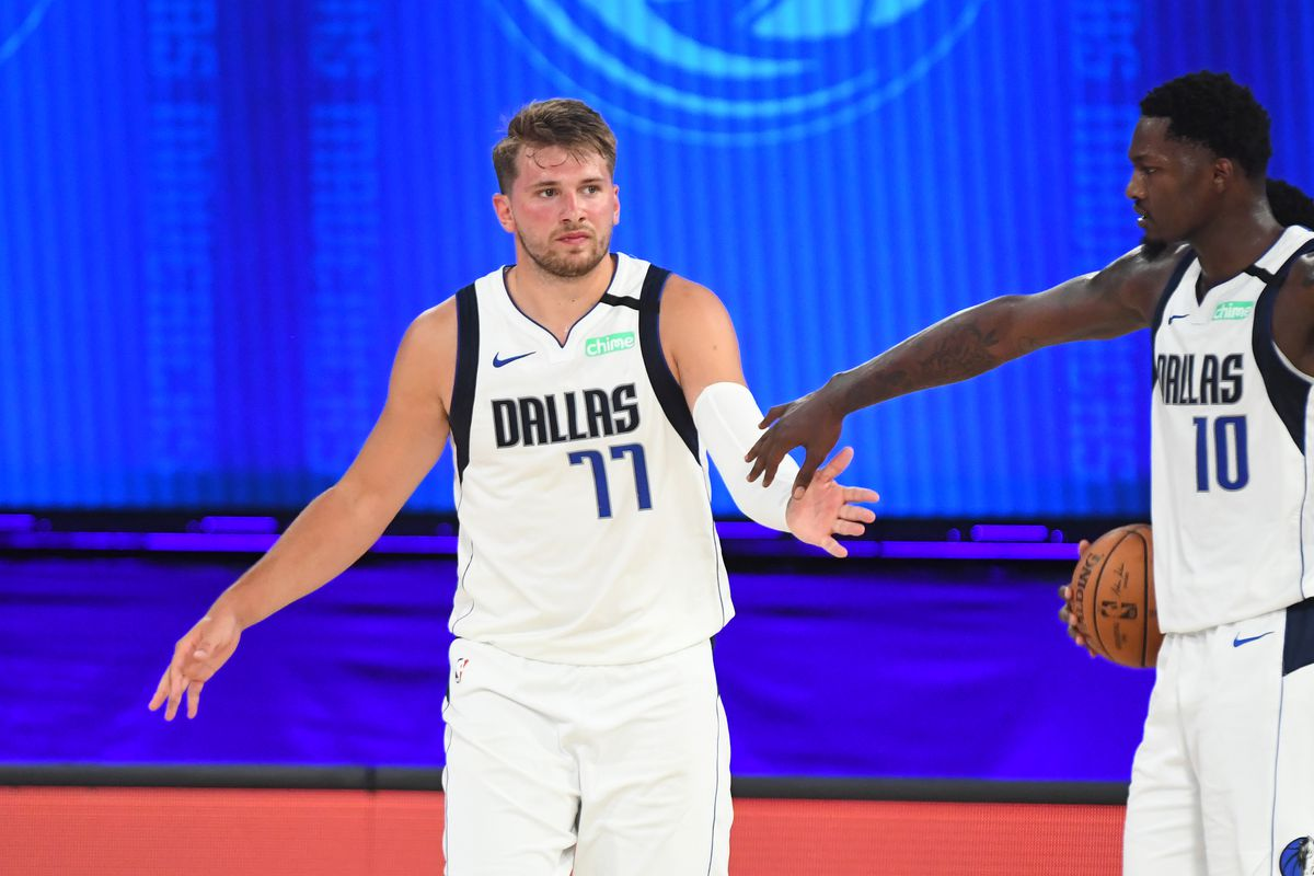 Luka Doncic of the Dallas Mavericks high-fives Dorian Finney-Smith of the Dallas Mavericks during a scrimmage on July 26, 2020 at HP Field House at ESPN Wide World of Sports in Orlando, Florida.