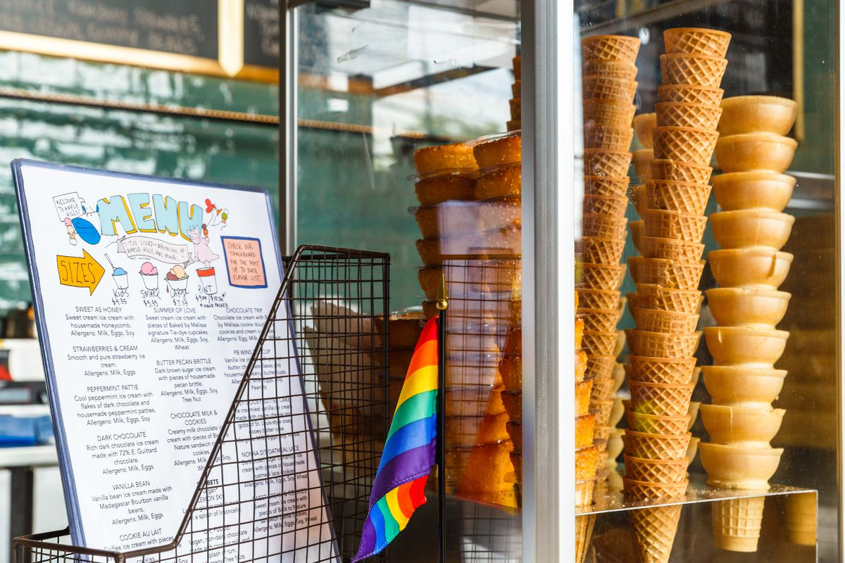 A menu of ice cream flavors next to a stack of ice cream cones inside one of Ample Hills's shops in Brooklyn