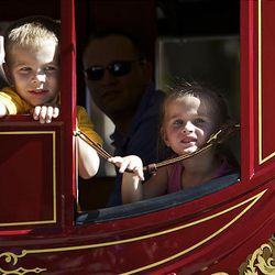 Two young participants in the parade wave to the crowd from their perch in a horse drawn stagecoach as spectators watch the floats, horses and celebrities participate in the Days of '47 Parade in Salt Lake City Saturday.