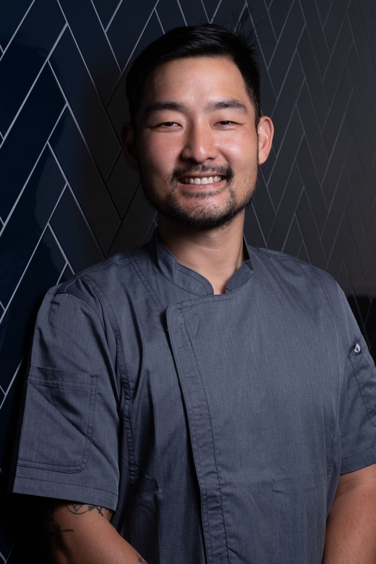A portrait of a smiling male chef in a blue chef's coat.