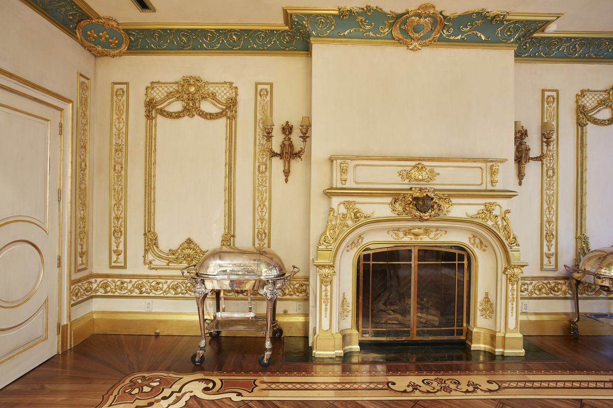 A wood-burning fireplace with golden wall decorations and hardwood floors.