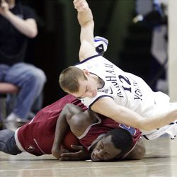 BYU's Josh Sharp, top, and Loyola Marymount Lions forward Ashley Hamilton compete for a loose ball.