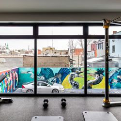 The fitness center features floor-to-ceiling windows and overlooks the mural-painted parking garage.