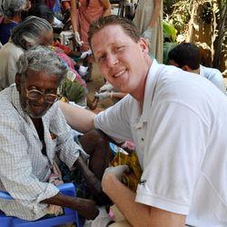 Former NBA player Shawn Bradley with a man at a leper colony in Dethel Nagar, India.