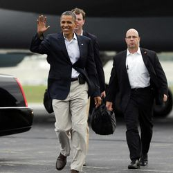 President Barack Obama waves to supporters as he walks across the tarmac to greet them upon his arrival at Toledo Express Airport, Sunday, Sept. 2, 2012, in Toledo, Ohio.