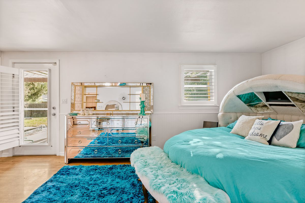 A master bedroom with a round, bright teal bed, darker teal rug, and a shiny all-silver chest of drawers.