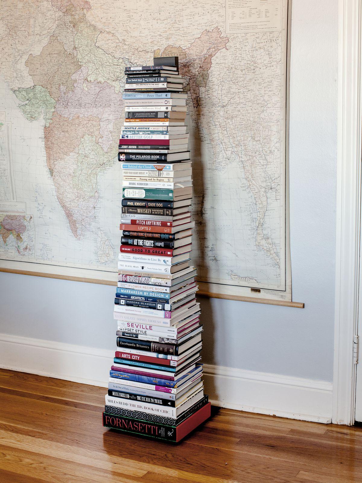 A tower bookshelf holds many books.