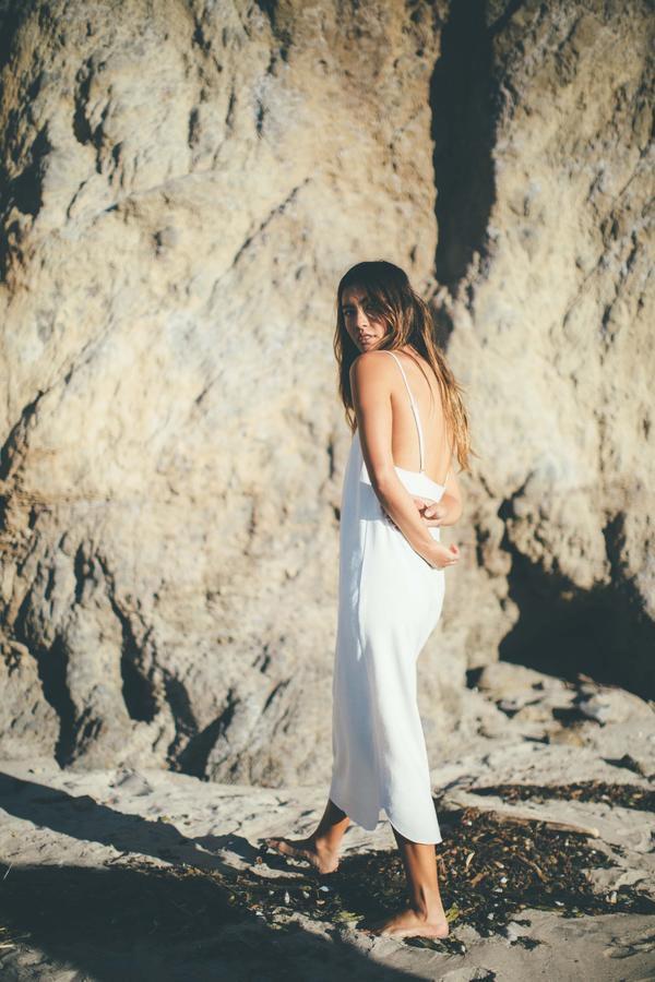 A woman wears a slip dress on the beach