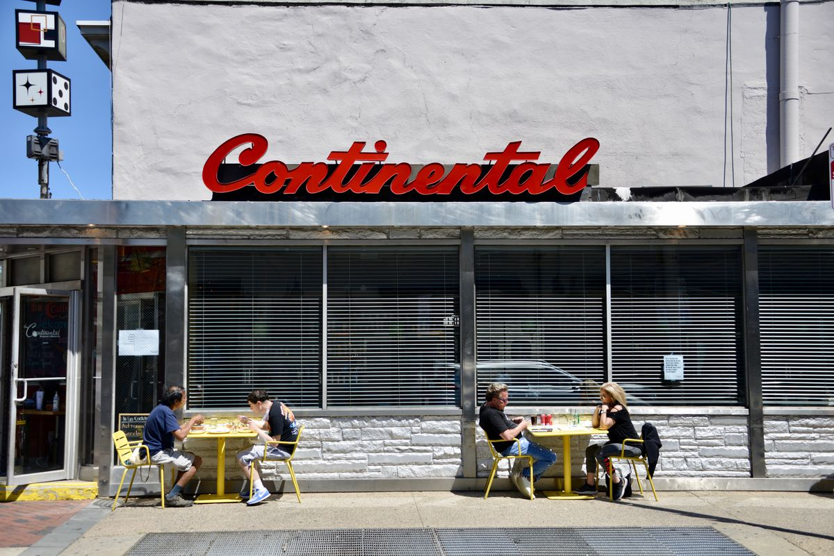outside of restaurant with sidewalk tables and red retro sign that says continental