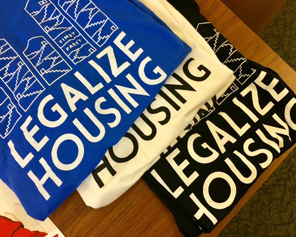 """conference swag: shirts with """"legalize housing"""" slogan."""