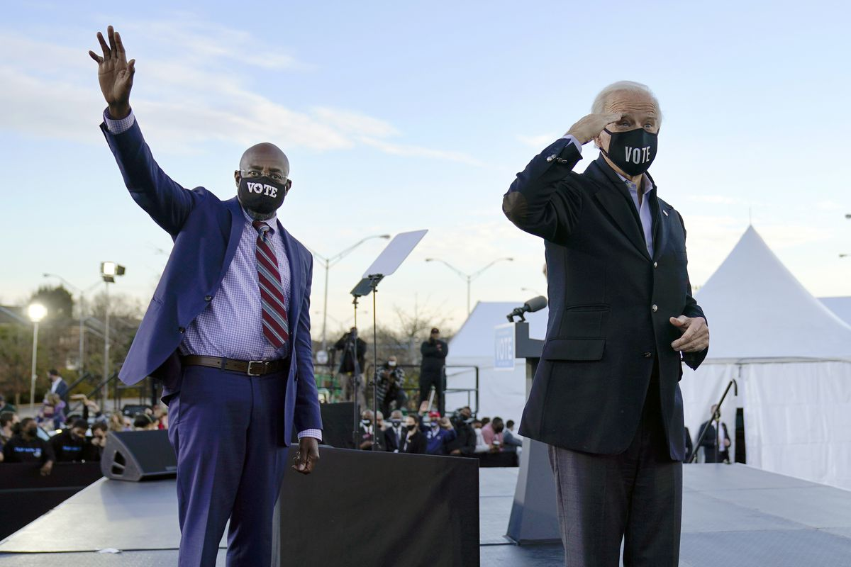 In this Monday, Jan. 4, 2021 file photo, President-elect Joe Biden, right, campaigns for Senate candidates Raphael Warnock, left, and Jon Ossoff, not pictured, in Atlanta.