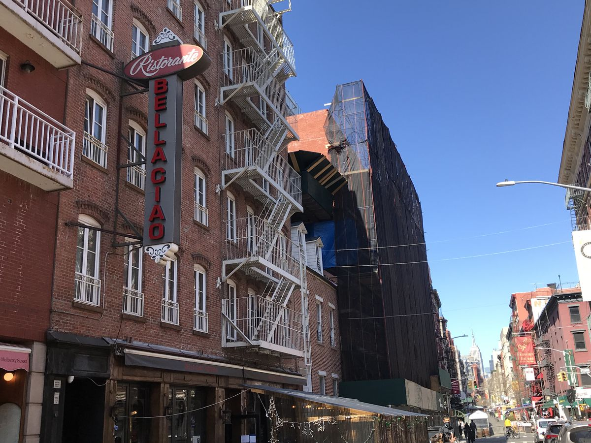 A restaurant located on the first floor of a city apartment complex, with fire escapes and a vintage sign that reads Bella Ciao in capital letters