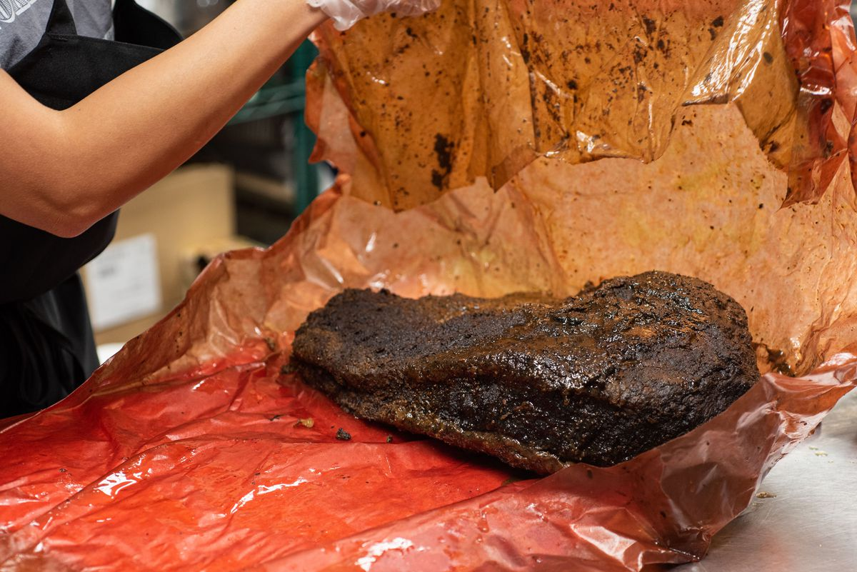 Unwrapping a large brisket from off-red paper.