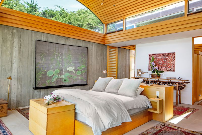 A white bed sits on a wooden platform in a room with concrete walls and barrel vaulted ceilings.