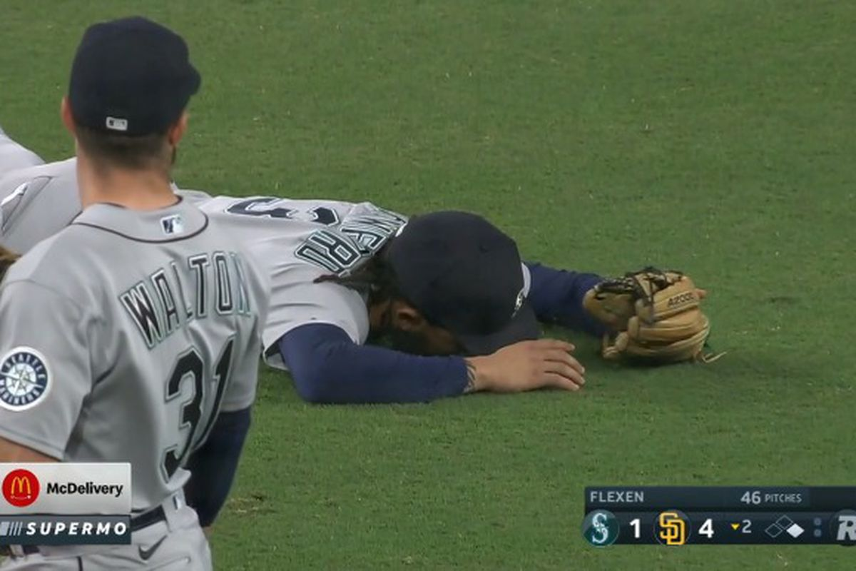 An MLB player lies face down on the grass while his teammate looks on