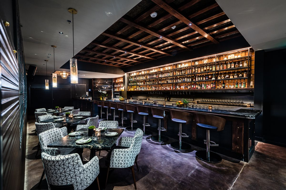 Patterned chairs, dark stone tables, and the bar inside basement-level Dram & Grain