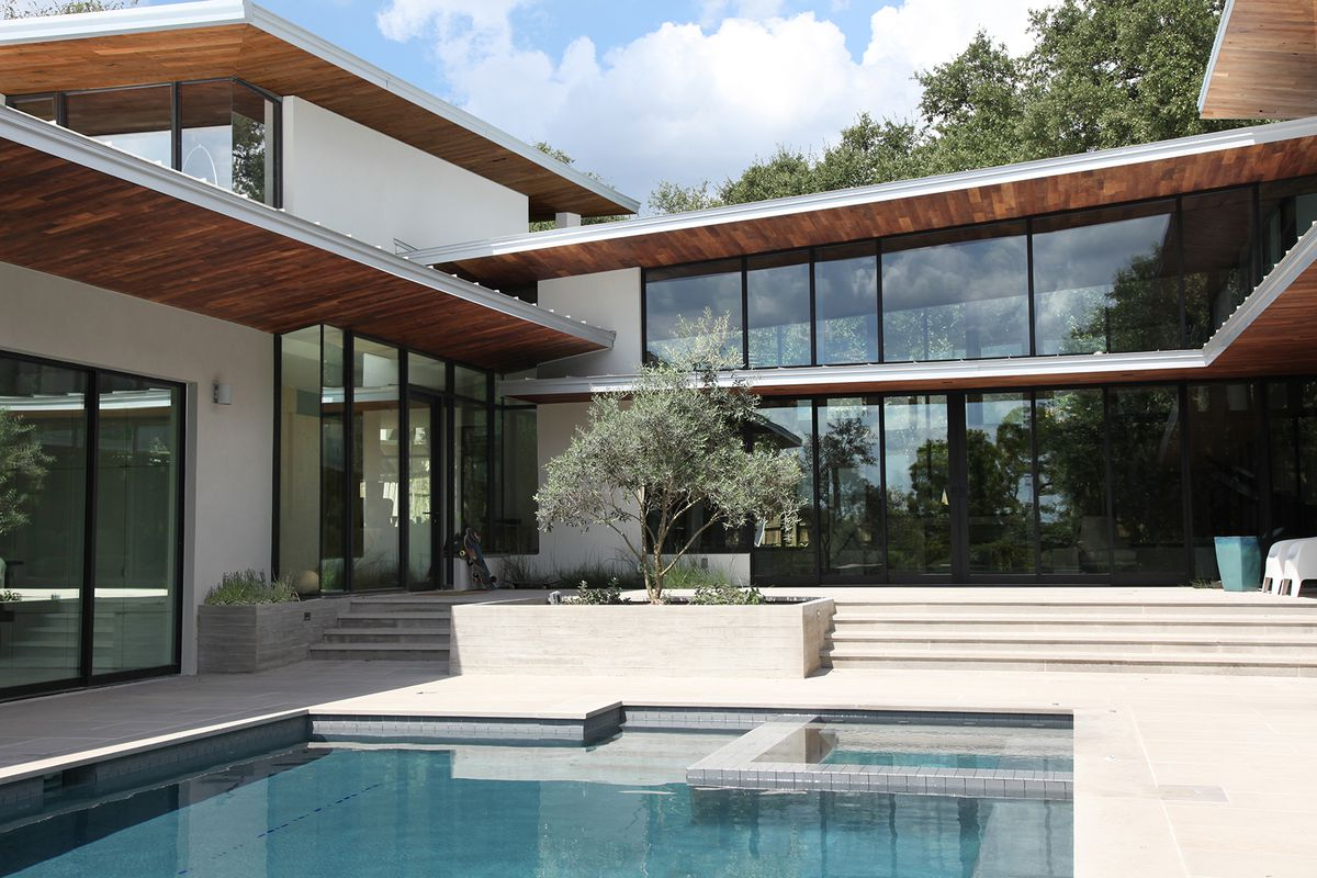 contemporary pool surrounded by glass house and wooden deck covers