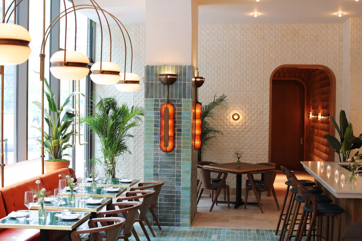A colorful indoor dining room with custom light fixtures, several tables set for service, and custom tiling on its floors and walls.