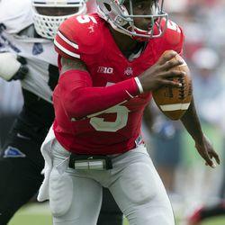 Ohio State Buckeyes quarterback Braxton Miller (5) tries to evade pressure from Buffalo Bulls linebacker Khalil Mack (46) at Ohio Stadium. Ohio State won the game 40-20.