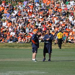 Broncos Defensive Coordinator Wade Phillips (orange hat) and Broncos Head Coach Gary Kubiak talk to each other before the joint practice with the San Francisco 49ers.