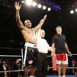 Evander Holyfield, left, celebrates his win over former Massachusetts Gov. Mitt Romney during the Charity Vision Fight Night event in Salt Lake City, Friday, May 15, 2015.