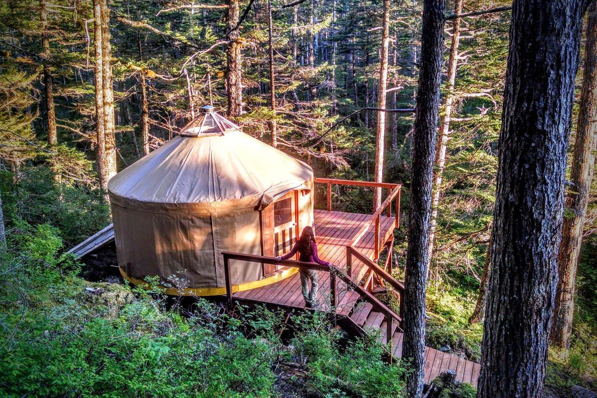 An aerial view of a yurt in a forest. The facade of the yurt is tan and there is a wooden deck.