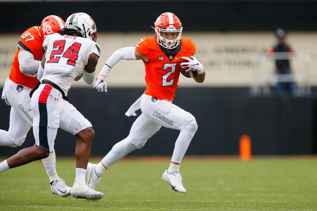 Wide receiver Tylan Wallace #2 of the Oklahoma State Cowboys runs for seven yards on the last drive of the game against defensive back Adam Beck #24 of the Texas Tech Red Raiders in the fourth quarter at Boone Pickens Stadium on November 28, 2020 in Stillwater, Oklahoma. OSU won 50-44.