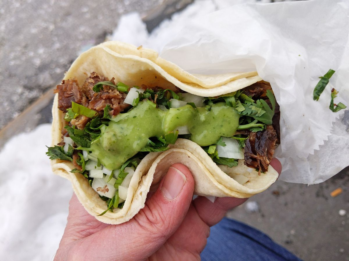 A hand holds a double tortilla taco with guacamole on top and snow and sidewalk in the background.