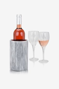 A bottle of wine in a wine chiller next to 2 wine glasses