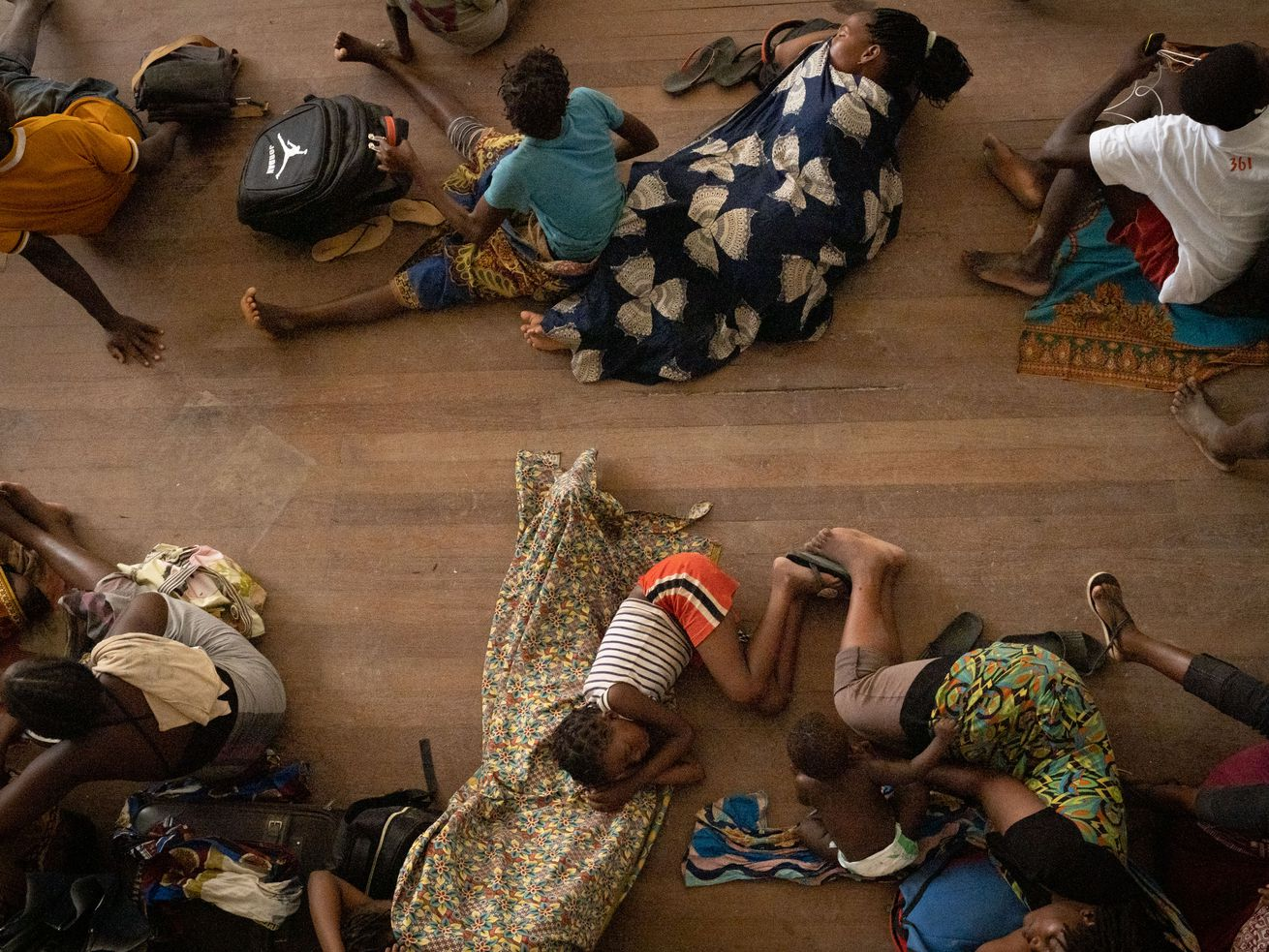 People from the isolated district of Buzi take shelter in the Samora M. Machel secondary school used as an evacuation center in Beira, Mozambique, on March 21, 2019, following the devastation caused by Cyclone Idai.