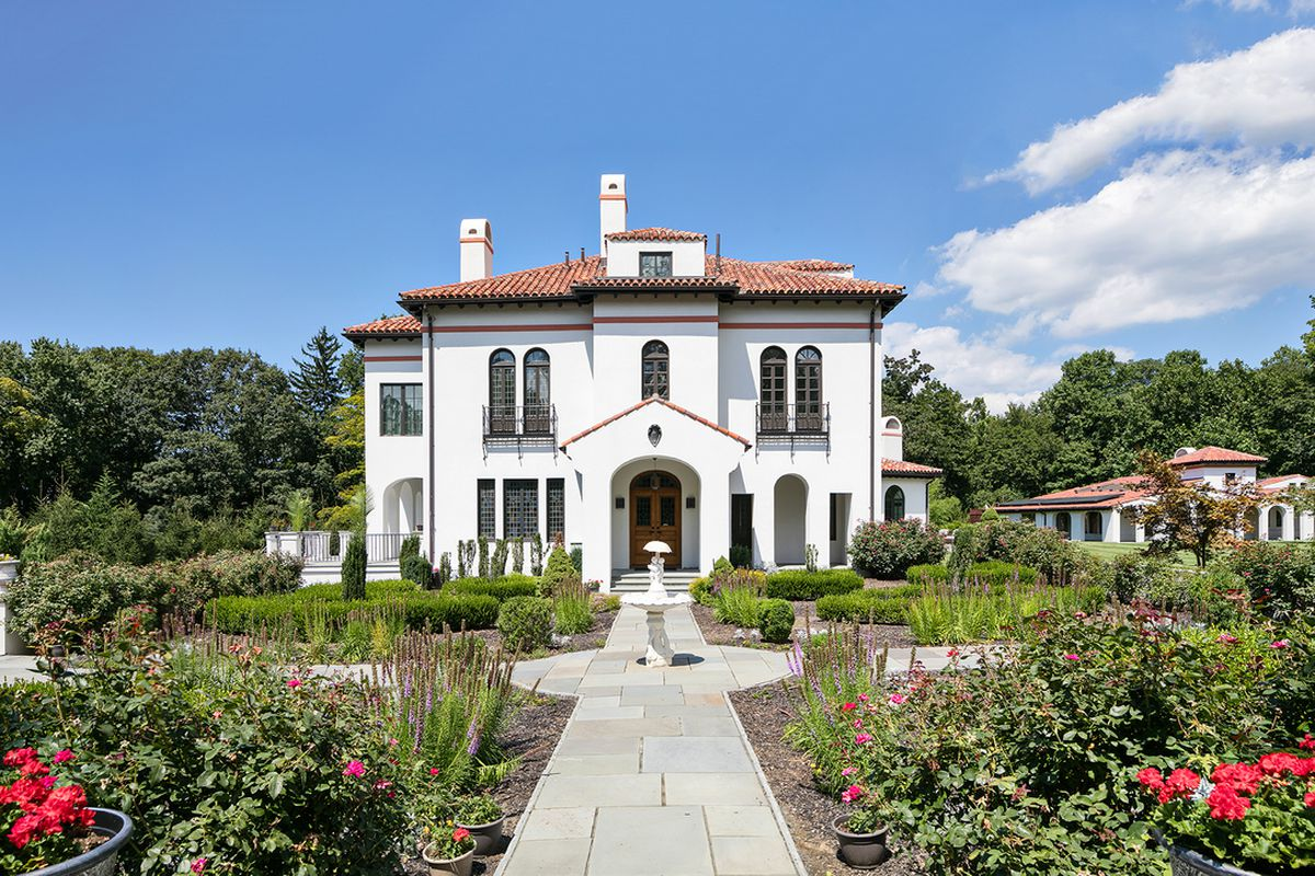 Shot of exterior of Mediterranean style home with white walls, arched windows, and terra cotta shingled roof. A landscaped formal garden sits in the foreground.