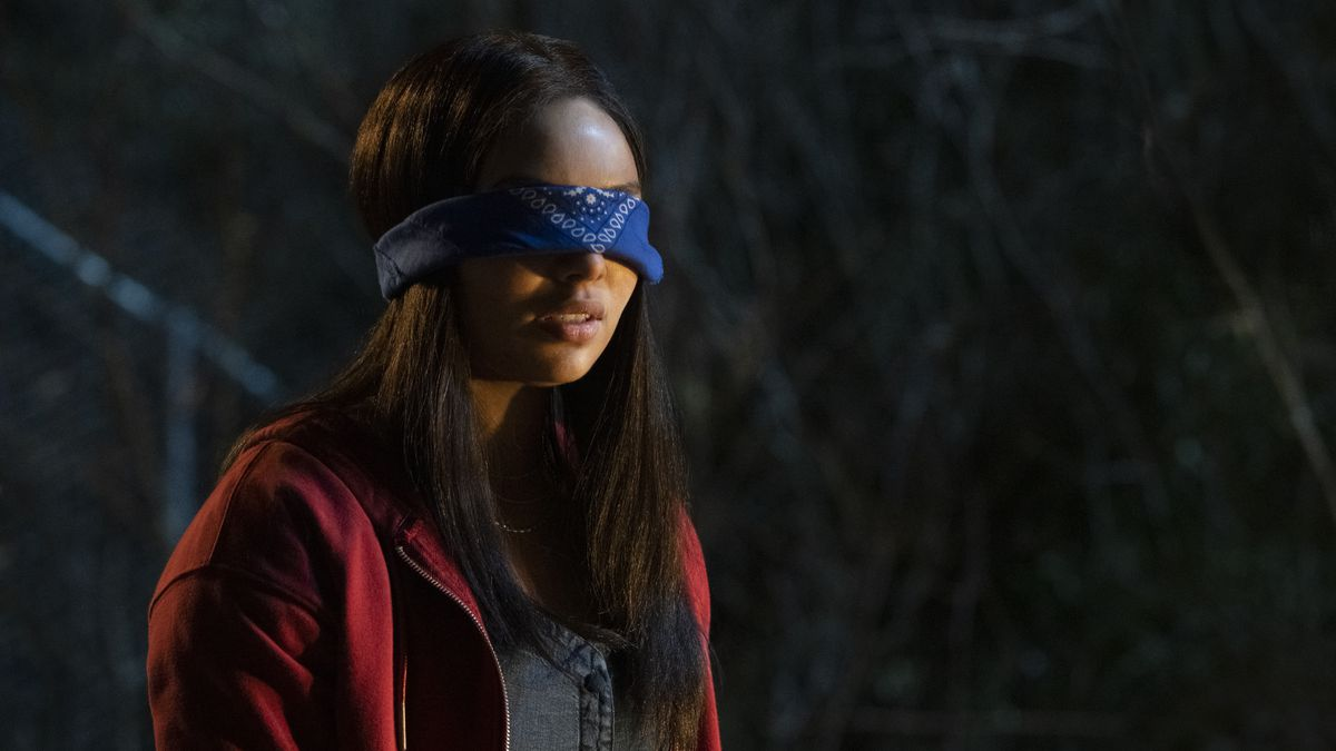 A long-haired teenage girl in a red jacket and bright blue bandana blindfold in Panic