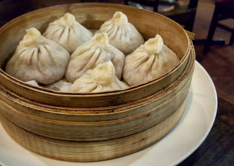 A wooden steamer at Dumpling Cafe holds half a dozen plump soup dumplings