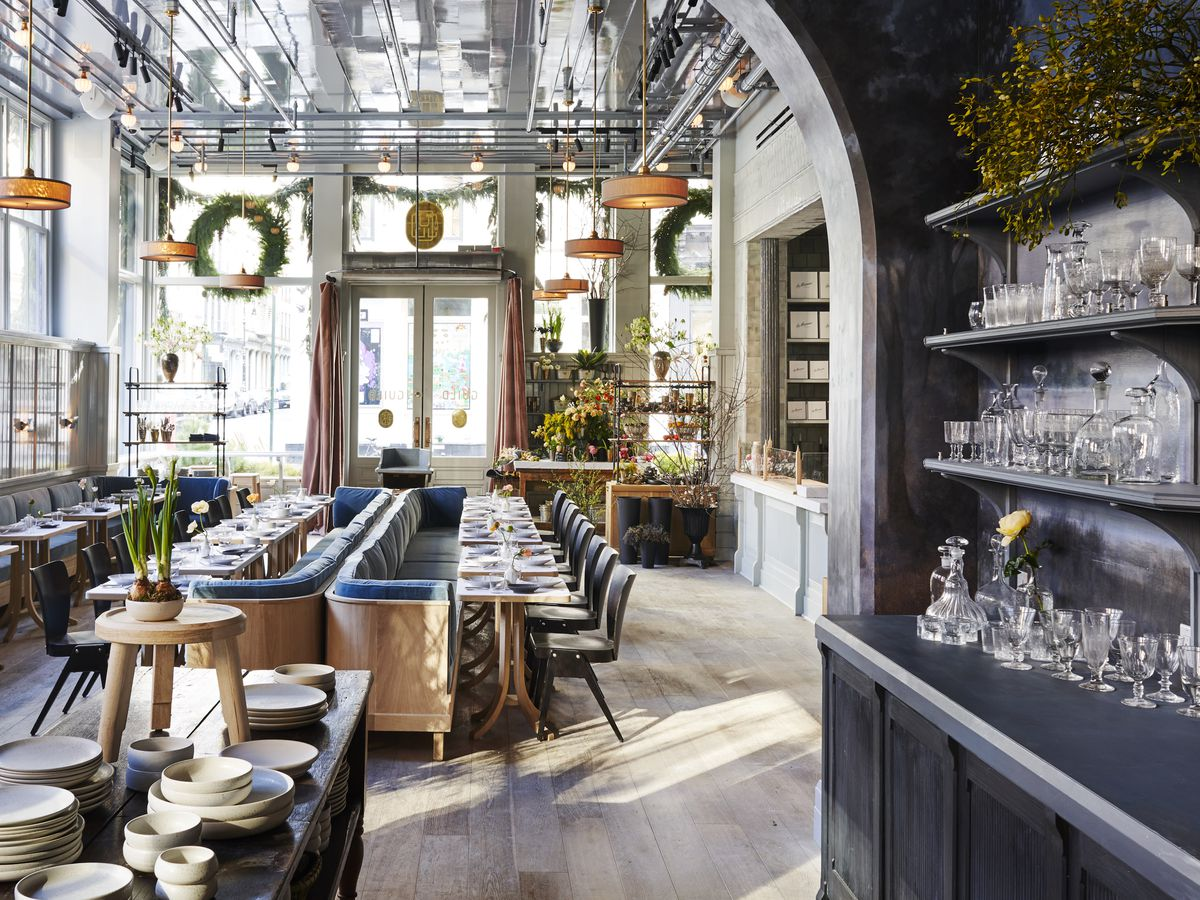 The airy interior of a restaurant with high ceilings and a lot of natural light streaming in through windows.
