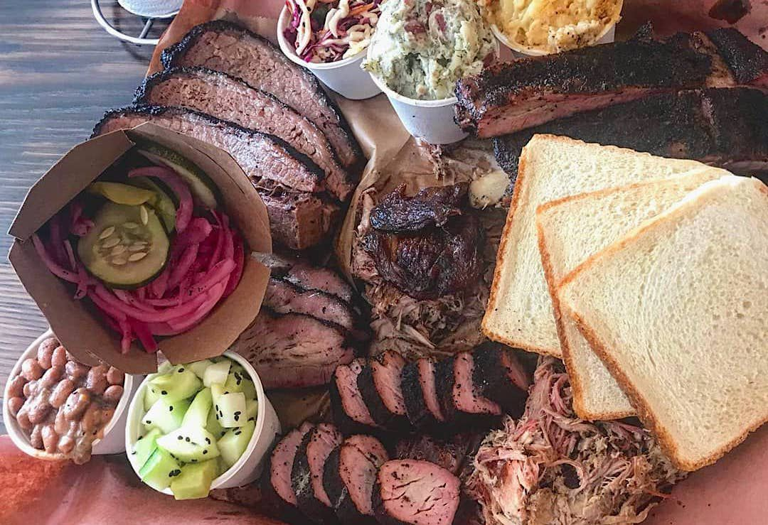 Array of smoked meats with sides and bread