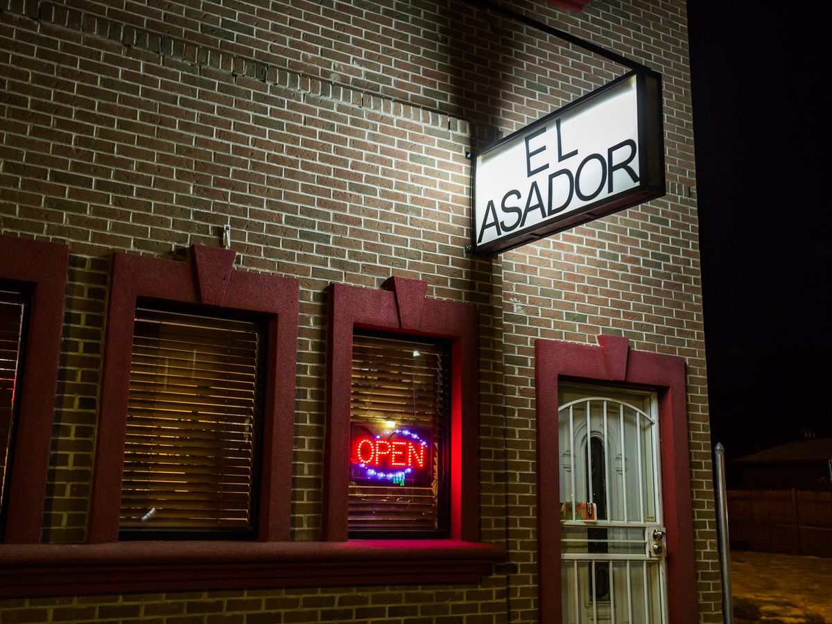 The sign for Al Asador on a brick building at night.