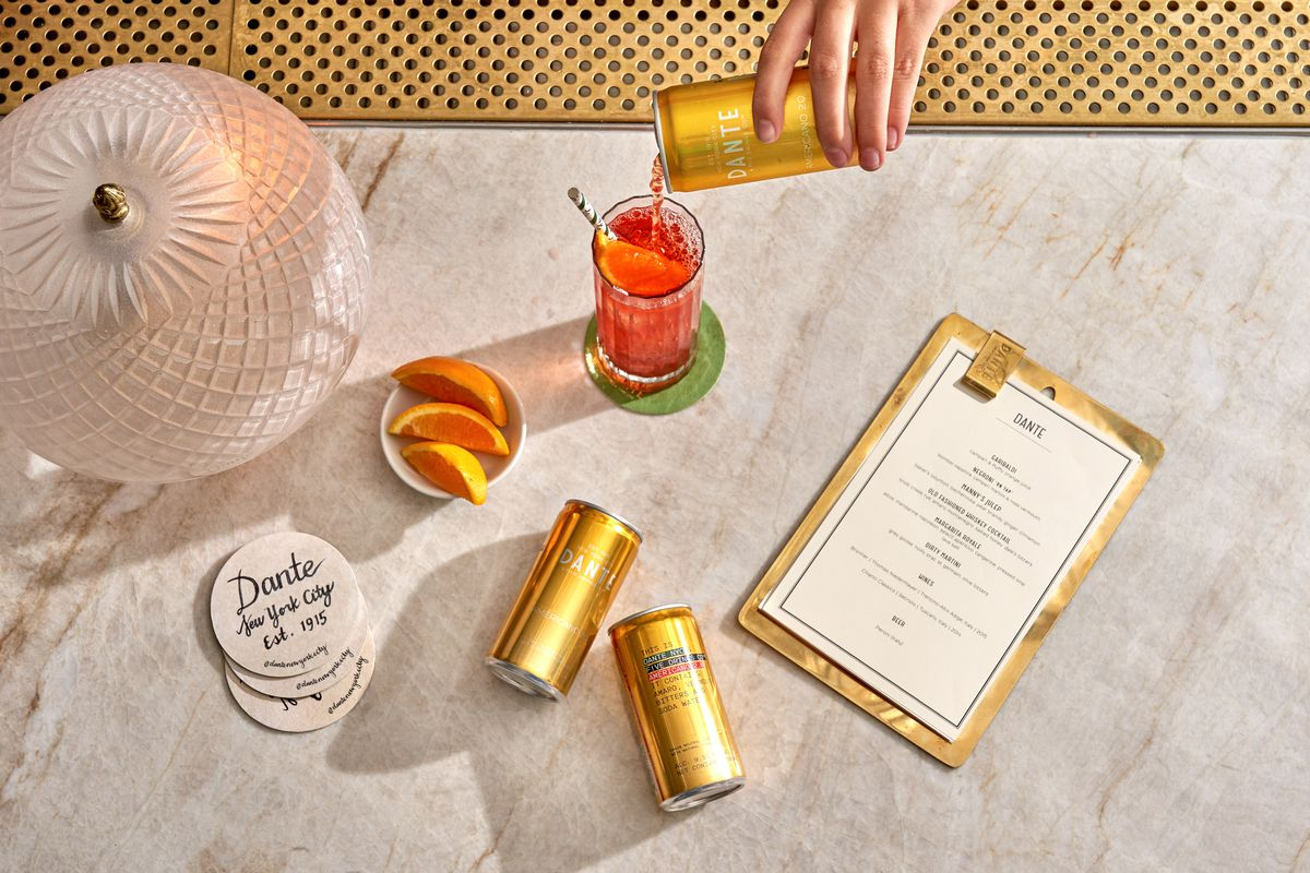 An overhead photograph of two gold canned cocktails, stacked white coasters, a menu, and off-screen a hand pours a red drink into a cocktail glass