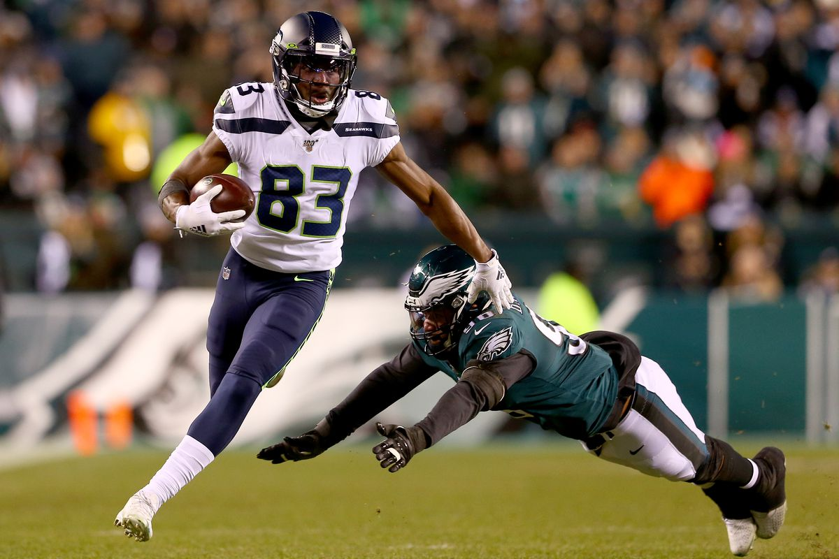 David Moore #83 of the Seattle Seahawks carries the ball against Derek Barnett #96 of the Philadelphia Eagles during the NFC Wild Card Playoff game at Lincoln Financial Field on January 05, 2020 in Philadelphia, Pennsylvania.