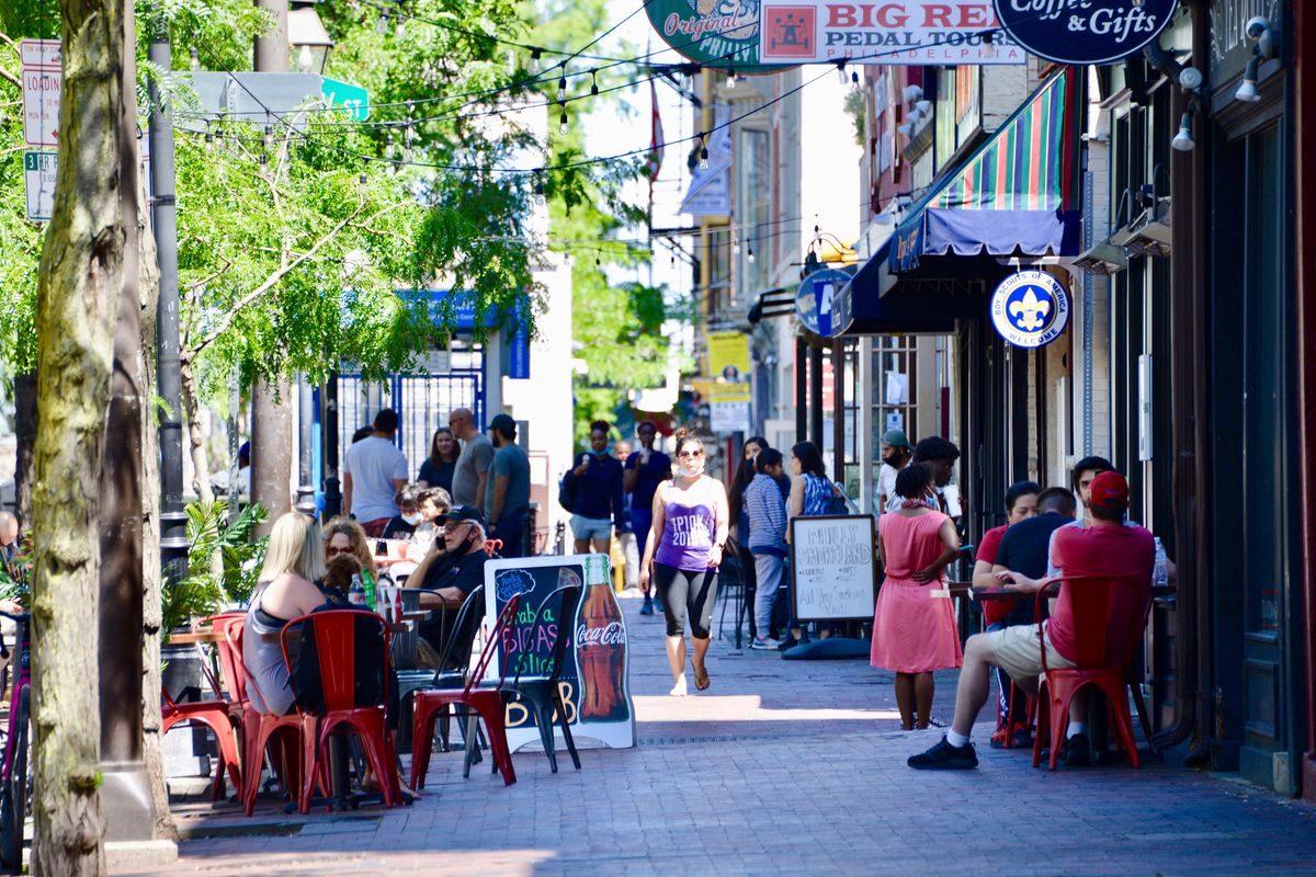 restaurants with outdoor tables in old city and people walking down the street
