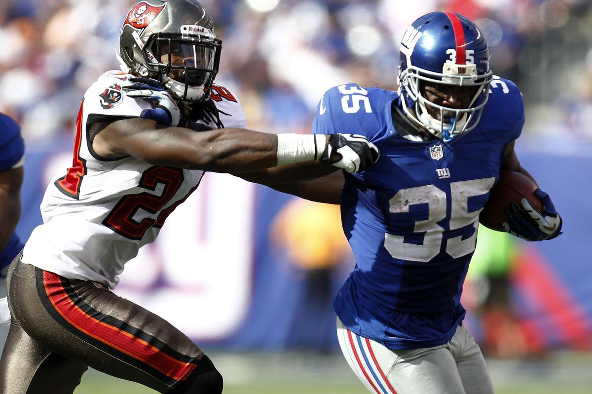 EAST RUTHERFORD, NJ - SEPTEMBER 16:   Andre Brown of the New York Giants holds off  Mark Barron of the Tampa Bay Buccaneers during a game at MetLife Stadium on September 16, 2012 in East Rutherford, New Jersey. (Photo by Jeff Zelevansky/Getty Images)