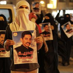 """Bahraini anti-government protesters carry images of jailed hunger-striker Abdulhadi al-Khawaja that read """"Freedom or martyrdom"""" during a demonstration Sunday, April 8, 2012, outside the Interior Ministry in Manama, Bahrain. Bahrain on Sunday rejected the Danish government's request to transfer the jailed activist who is on a nearly two-month hunger strike to Denmark for treatment, the official news agency in the Gulf kingdom said."""