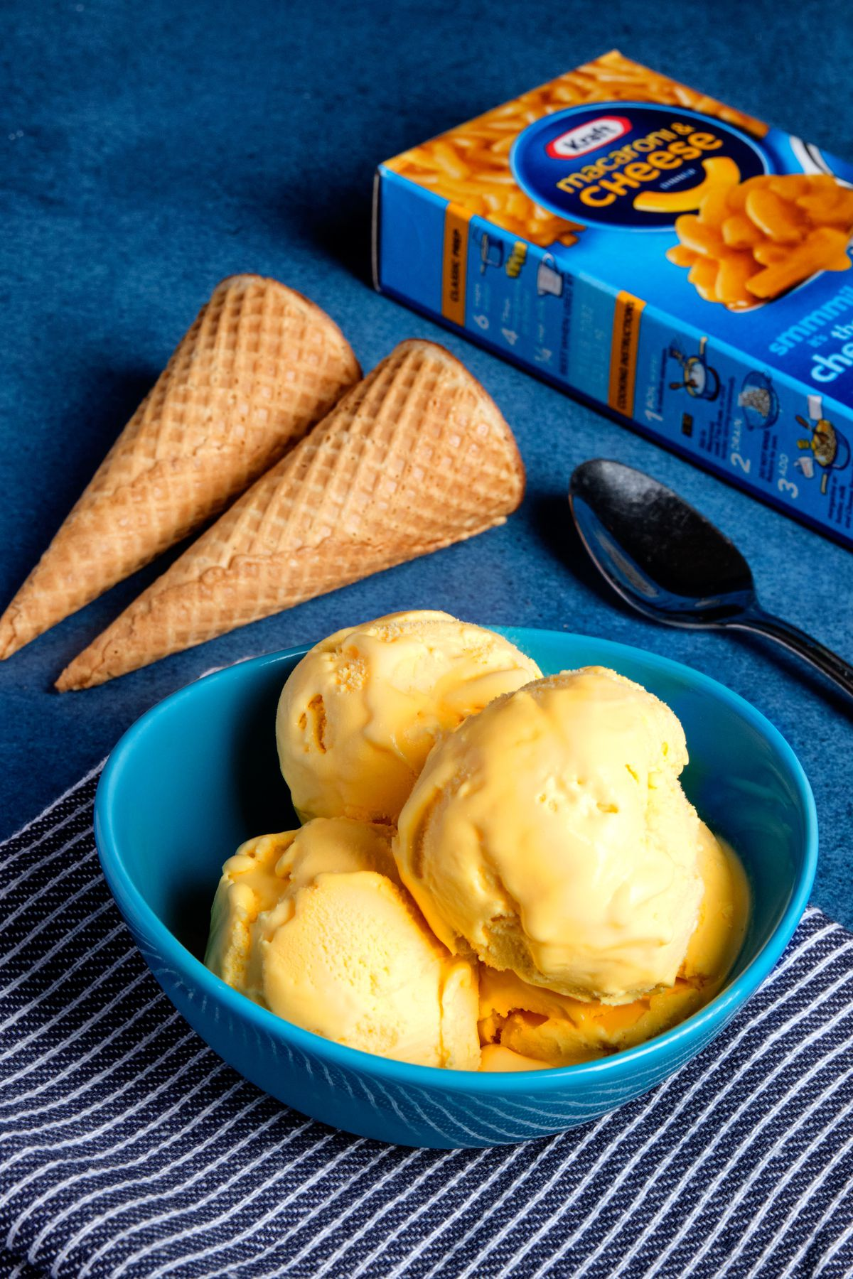 Three scoops of mac and cheese flavored ice cream in a bowl next to a box of Kraft Mac and Cheese, an ice cream scoop and two ice cream cones.